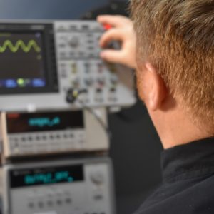 Technician working in front of an oscilloscope and integrating sphere test bench